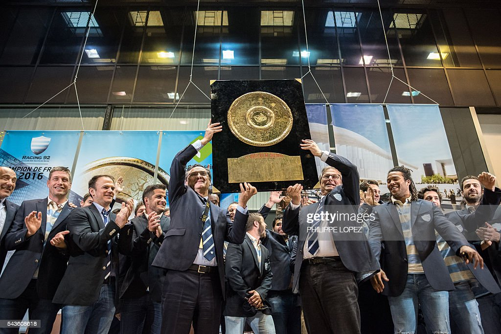 Racing Metro 92's French President Jacky Lorenzetti (C,R) and head of the Hauts-de-Seine general council Patrick Devedjian (C,L) hold the 'Bouclier de Brennus' (Brennus Shield) as they celebrate with some of the team's players at the Hauts-de-Seine government house following the club victory in the French Top14 rugby union final match Toulon vs Racing 92, in Nanterre on the outskirts of Paris on June 29, 2016. / AFP / PHILIPPE