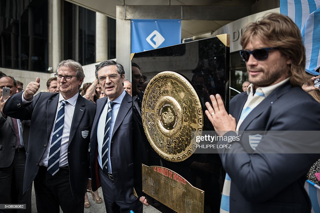 Racing Metro 92's French President Jacky Lorenzetti (L), head of the Hauts-de-Seine general council Patrick Devedjian (2L) and Racing Metro 92 French hooker Dimitri Szarzewski pose with the 'Bouclier de Brennus' (Brennus Shield) outside the Hauts-de-Seine government house following the club victory in the French Top14 rugby union final match Toulon vs Racing 92, in Nanterre on the outskirts of Paris on June 29, 2016. / AFP / PHILIPPE