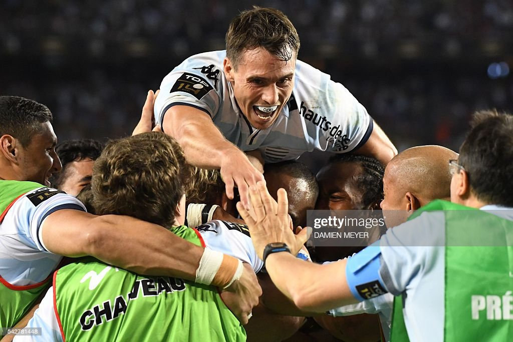 Racing Metro 92's New Zealander wing Joe Rokocoko (C) is congratulated by teammate Racing Metro 92's Argentine wing Juan Imhoff (top) after scoring his try during the French Top14 rugby union final match Toulon vs Racing 92 at the Camp Nou stadium in Barcelona on June 24, 2016. / AFP / DAMIEN