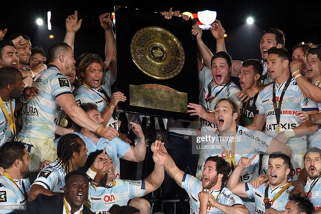 Racing Metro 92's players celebrate with the trophy after winning the French Top14 rugby union final match Toulon vs Racing 92 at the Camp Nou stadium in Barcelona on June 24, 2016. / AFP / LLUIS