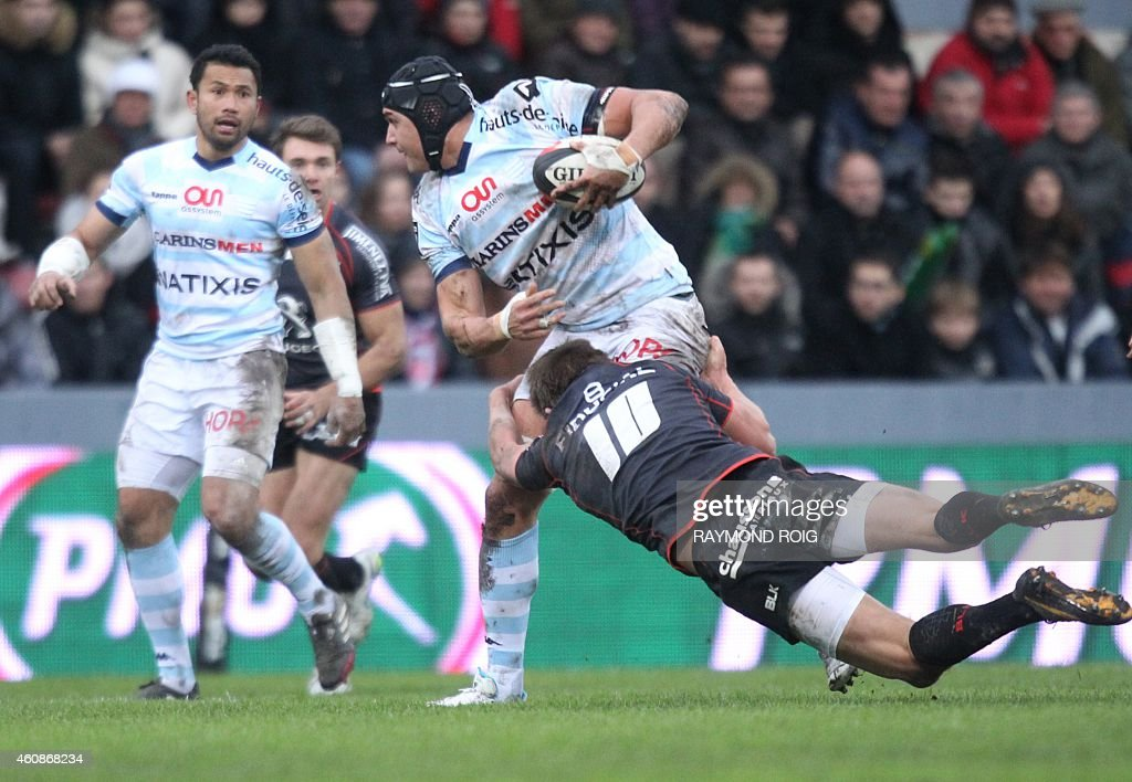 Racing Metro's South Afgrican hooker Juandre Kruger is tackled by Toulouse's British flyhalf Toby Flood during the French Top 14 rugby union match...