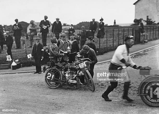 Racing motorcyclist P Weatherilt has a drink while his his Zenith machine is refuelled by Zenith chief engineer Freddie W Barnes at the Junior...