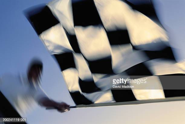 Racing official waving checkered flag (blurred motion), low angle view