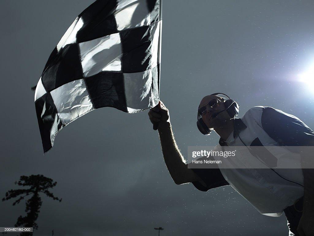 Racing official waving checkered flag : Stock Photo