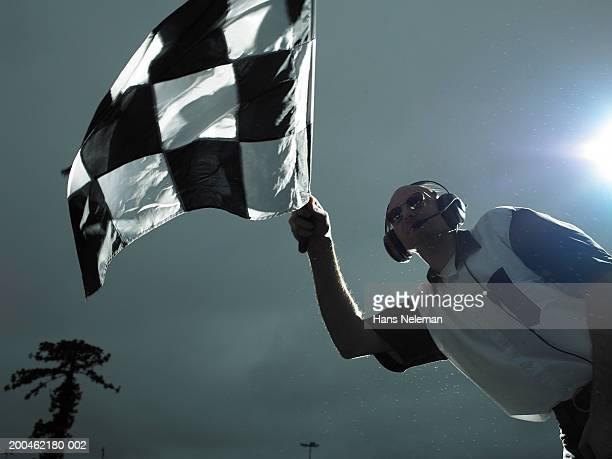 Racing official waving checkered flag