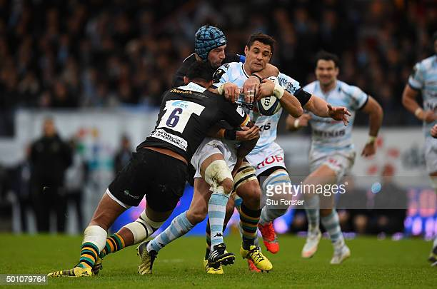Racing player Dan Carter is tackled by Courtney Lawes and Michael Paterson during the European Rugby Champions Cup match between Racing Metro 92 and...