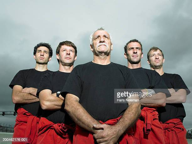 Racing team mechanics looking upwards