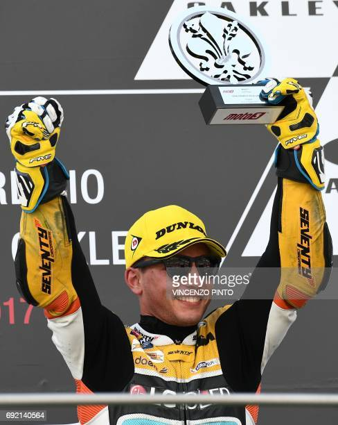 Racing Team rider Spanish Juanfran Guevara third celebrates on the podium after winning the Moto 3 Grand Prix at the Mugello race track on June 4...