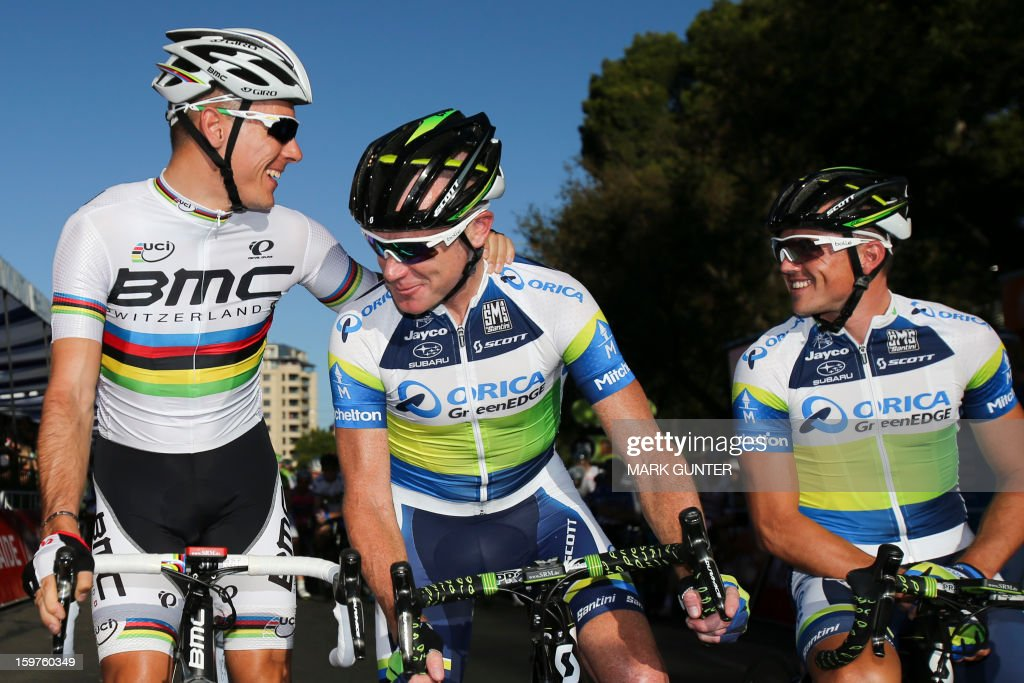BMC Racing Team's Philippe Gilbert (L) talks to Stuart O'Grady (C) and Simon Gerrans (R) from Orica-GreenEdge before the start of the 51km People's Choice Classic prior to the Tour Down Under in Adelaide on January 20, 2013. The six-stage Tour Down Under takes place from January 20 to 27. AFP PHOTO / Mark Gunter USE