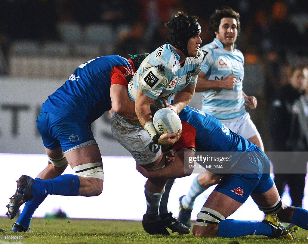 Racing-Metro's South African flanker Bernard Le Roux (C) is tackled by Grenoble's Australian lock Andrew Farley (L) during the French Top 14 rugby Union match Racing Metro 92 vs Grenoble on Mars 2, 2013 in the Yves du Manoir stadium in Colombes, northwest from Paris.