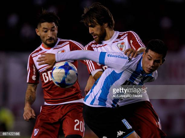 Racing's forward Brian Mansilla vies for the ball with River Plate's midfielder Leonardo Ponzio and defender Milton Casco during their Argentina...