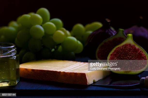 Raclette cheese served on the black slate board with honey, figs and grapes