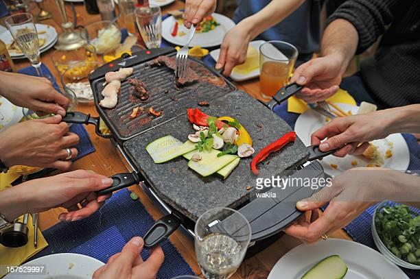 raclette mit vielen Händen