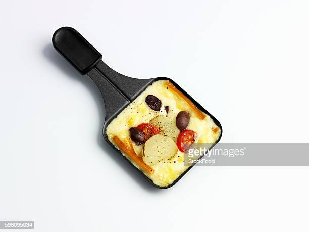 Raclette with potatoes, olives and tomatoes