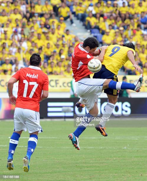 Radamel Falcao of Colombia and Eugenio Mena of Chile fight for the ball during a match between Colombia and Chile as part of the 17th round of the...