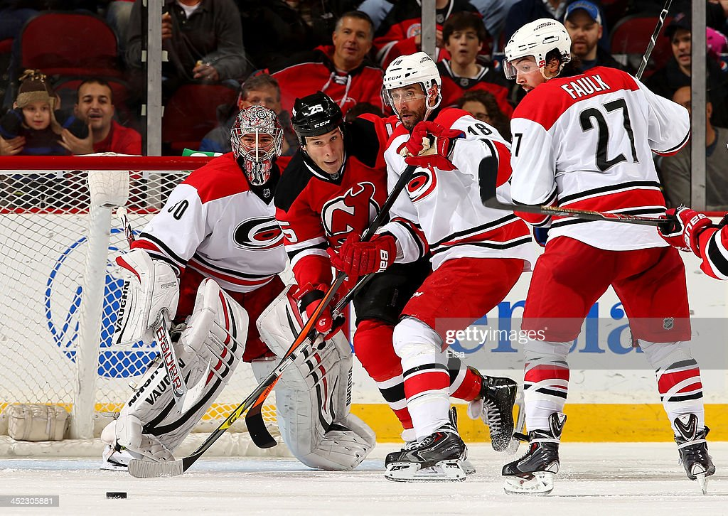Radek Dvorak #18 of the Carolina Hurricanes clears the puck as teammates Cam Ward #30 and Justin Faulk #27 defend against Cam Janssen #25 of the New Jersey Devils at Prudential Center on November 27, 2013 in Newark, New Jersey.The Carolina Hurricanes defeated the New Jersey Devils 4-3.
