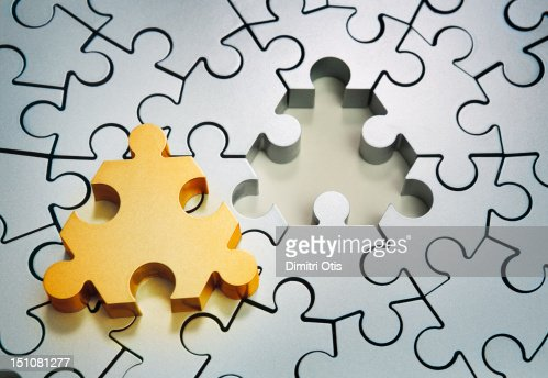 Radiating silver puzzle, gold centre piece aside : Stock Photo