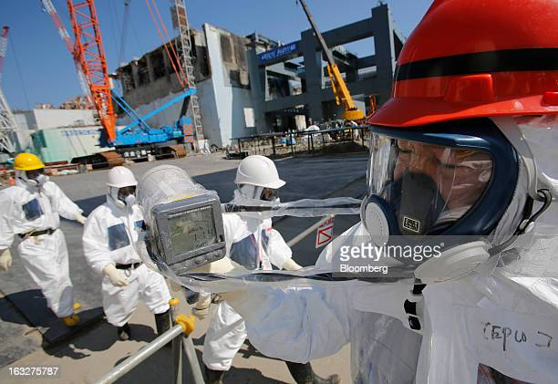 A radiation monitor reads 11400 microsieverts per hour as members of the media and Tokyo Electric Power Co employees wearing protective suits and...