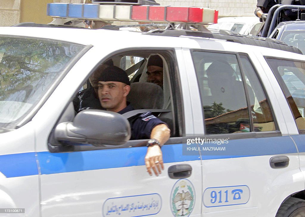 Radical Islamist cleric Abu Qatada (C-back) sits in the backseat of a police car outside the state security court in Amman on July 7, 2013. Abu Qutada pleaded not guilty to terror charges pressed by Jordanian military prosecutors just hours after his deportation from Britain, his lawyer said. Abu Qatada, who had been in and out of British prisons since 2002 even though he was never convicted of any offence, had once been described as now slain Al-Qaeda leader Osama bin Laden's right-hand man in Europe.