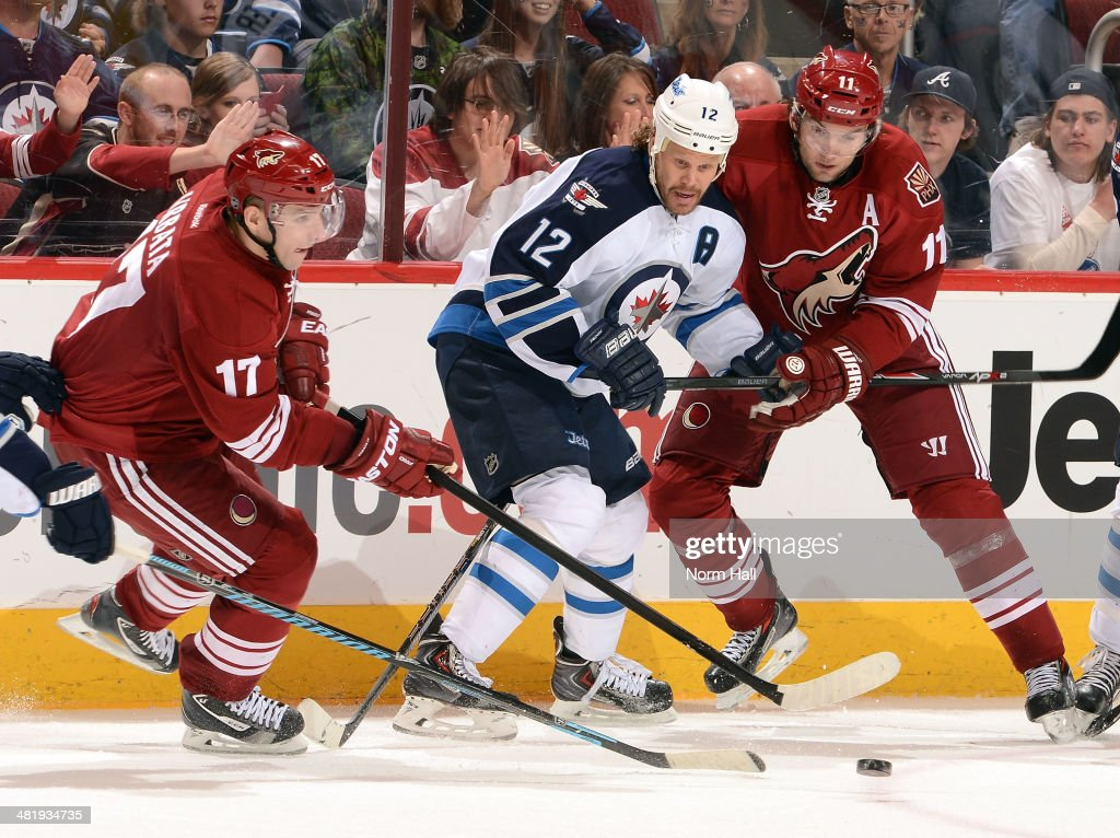 <a gi-track='captionPersonalityLinkClicked' href=/galleries/search?phrase=Radim+Vrbata&family=editorial&specificpeople=204716 ng-click='$event.stopPropagation()'>Radim Vrbata</a> #17 and <a gi-track='captionPersonalityLinkClicked' href=/galleries/search?phrase=Martin+Hanzal&family=editorial&specificpeople=2109469 ng-click='$event.stopPropagation()'>Martin Hanzal</a> #11 of the Phoenix Coyotes battle for the puck with <a gi-track='captionPersonalityLinkClicked' href=/galleries/search?phrase=Olli+Jokinen&family=editorial&specificpeople=202946 ng-click='$event.stopPropagation()'>Olli Jokinen</a> #12 of the Winnipeg Jets at Jobing.com Arena on April 1, 2014 in Glendale, Arizona.