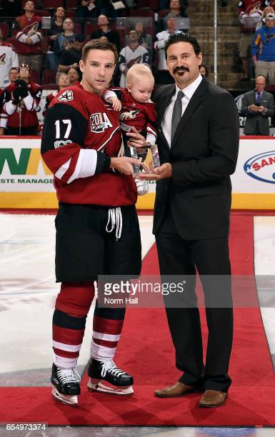 Radim Vrbata of the Arizona Coyotes is presented an award by NHL represenative George Parros to commomorate his 1000th NHL game during a ceremony...