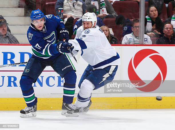 Radim Vrbata of the Vancouver Canucks passes the puck up ice past Eric Brewer of the Tampa Bay Lightning during their NHL game at Rogers Arena...
