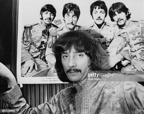 BBC Radio 1 disc jockey Stuart Henry in front of a publicity photo of his idols The Beatles from the album 'Sgt Pepper's Lonely Hearts Club Band'...