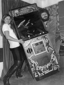 BBC Radio 1 presenter Dave Lee Travis helping Mandy Strong to carry a Space Invaders arcade machine at St George's Hotel Langham Place London 30th...