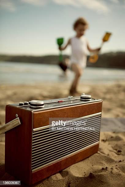 Radio and playing girl  on beach