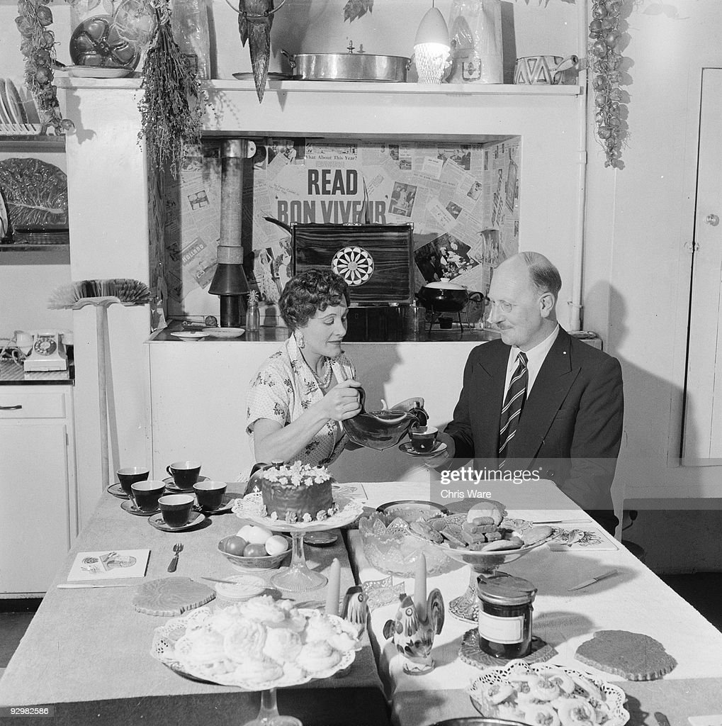 Radio and television cookery expert Fanny Cradock (1909 - 1994) serves tea to her bon viveur partner Johnnie Cradock (1904 - 1987) in their South Kensington home, London, 5th April 1956.