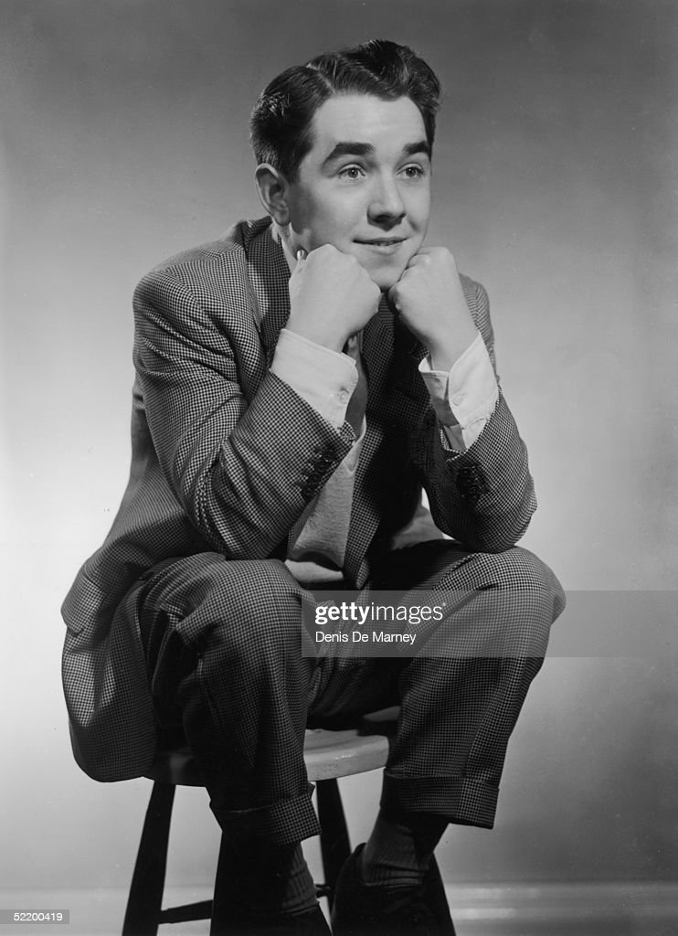 Radio comedian Ronnie Corbett perched on a stool with his head resting on his hands circa 1955