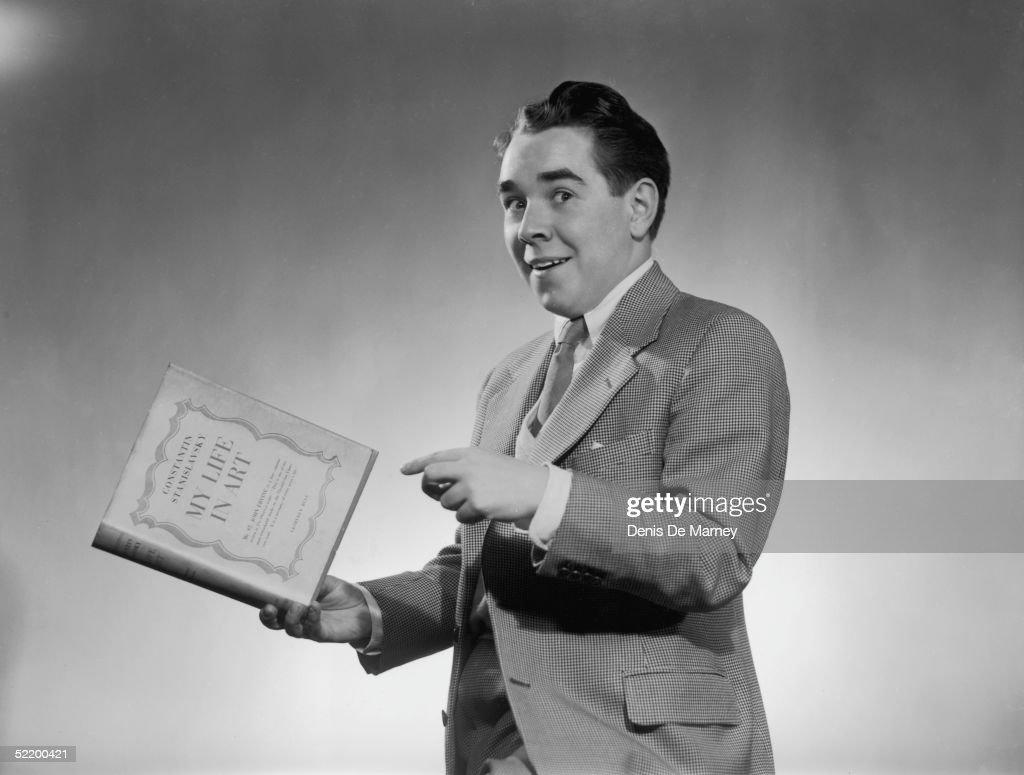 Radio comedian Ronnie Corbett posing with a book by Stanislavsky circa 1955