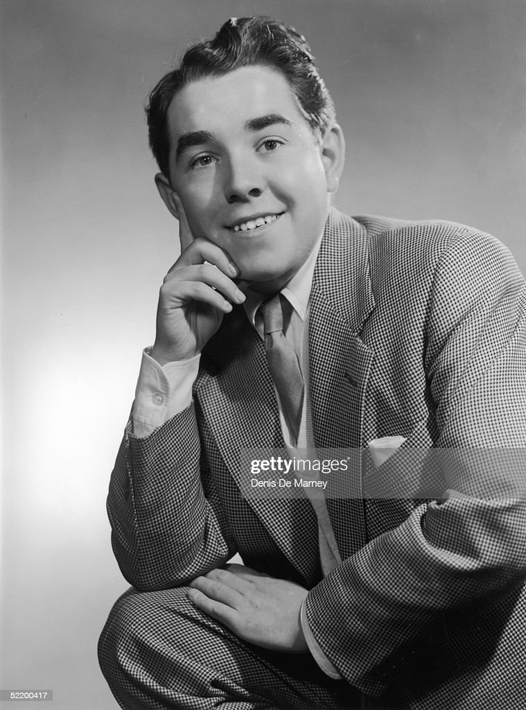 Radio comedian Ronnie Corbett posing with his finger on his cheek, circa 1955.