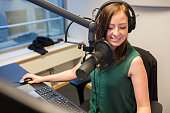 Happy young female radio jockey smiling while wearing headphones in studio