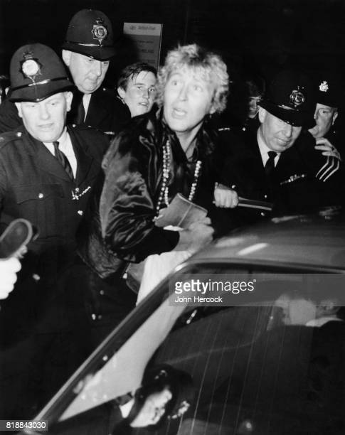 Radio London DJ Mike Lennox surrounded by police officers as he leaves Liverpool Street Station in London after the closure of Radio London 15th...