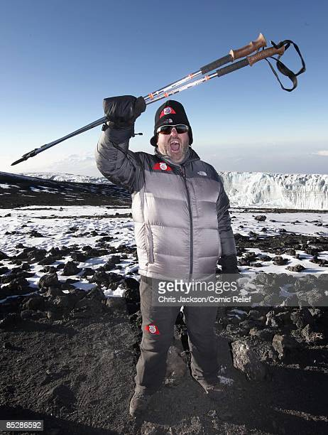 Radio One DJ Chris Moyles holds up his walking poles as he reaches the top of Mount Kilimanjaro on the seventh day of The BT Red Nose Climb of...