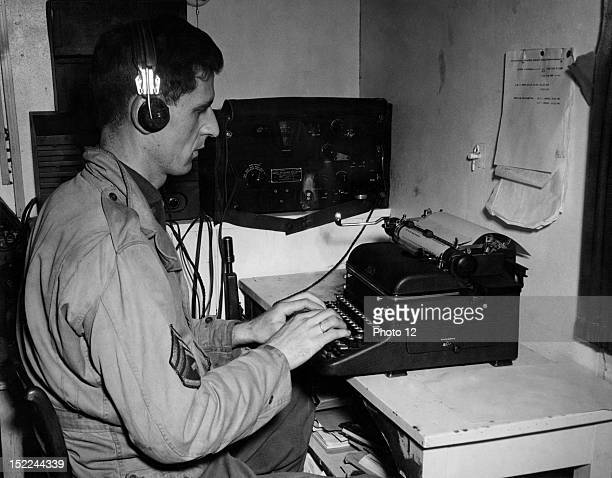 A US radio operator with 'Beachhead News' types out some late news just coming in over the air in Mutzig area December 1 1944
