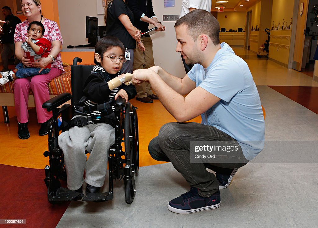 Z100 radio personality Garrett interacts with a patient during a visit to St. Mary's Hospital For Children on April 3, 2013 in New York City.