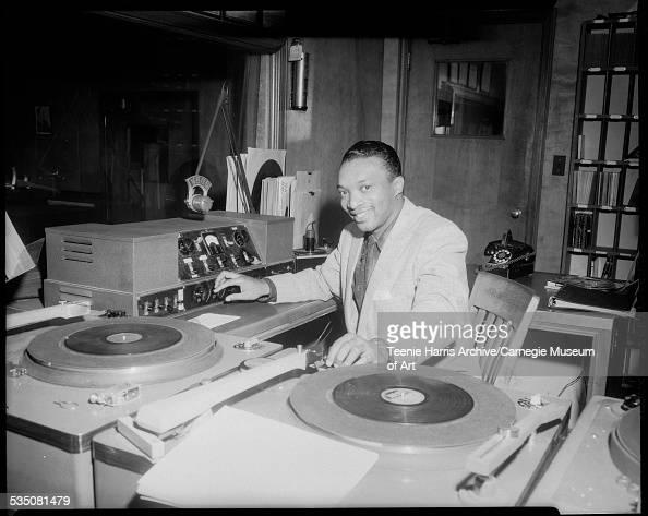 WHOD radio station disc jockey Walt Harper playing records and adjusting knob on equipment in Studio B Pittsburgh Pennsylvania 1951