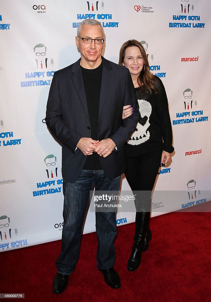 Radio / TV Personality Drew Pinsky (L) and his wife Susan Pinsky attend a surprise party for Larry King's 80th Birthday at Dodger Stadium on November 15, 2013 in Los Angeles, California.