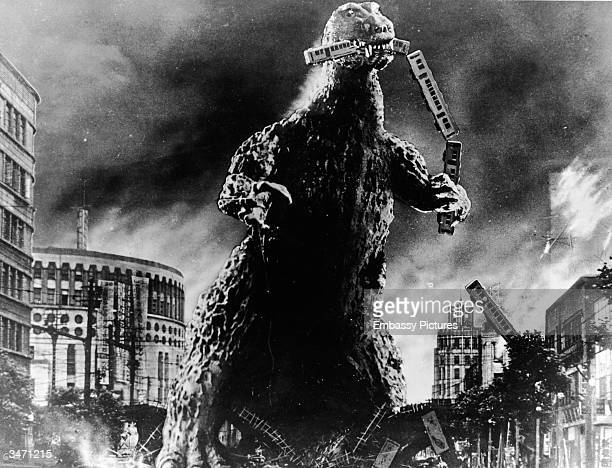 Radioactive monster Godzilla stomps through a city and eats a commuter train in a scene from 'Godzilla King of the Monsters' directed by Ishiro Honda...