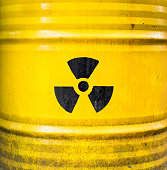 Radioactive sign on yellow nuclear waste barrel.