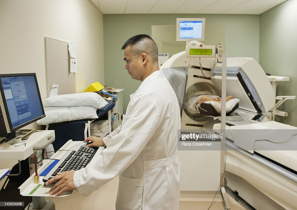 Radiologist enters data into MRI computer : Stock Photo
