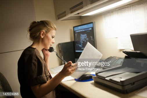 Radiologist on telephone checks notes : Stock Photo