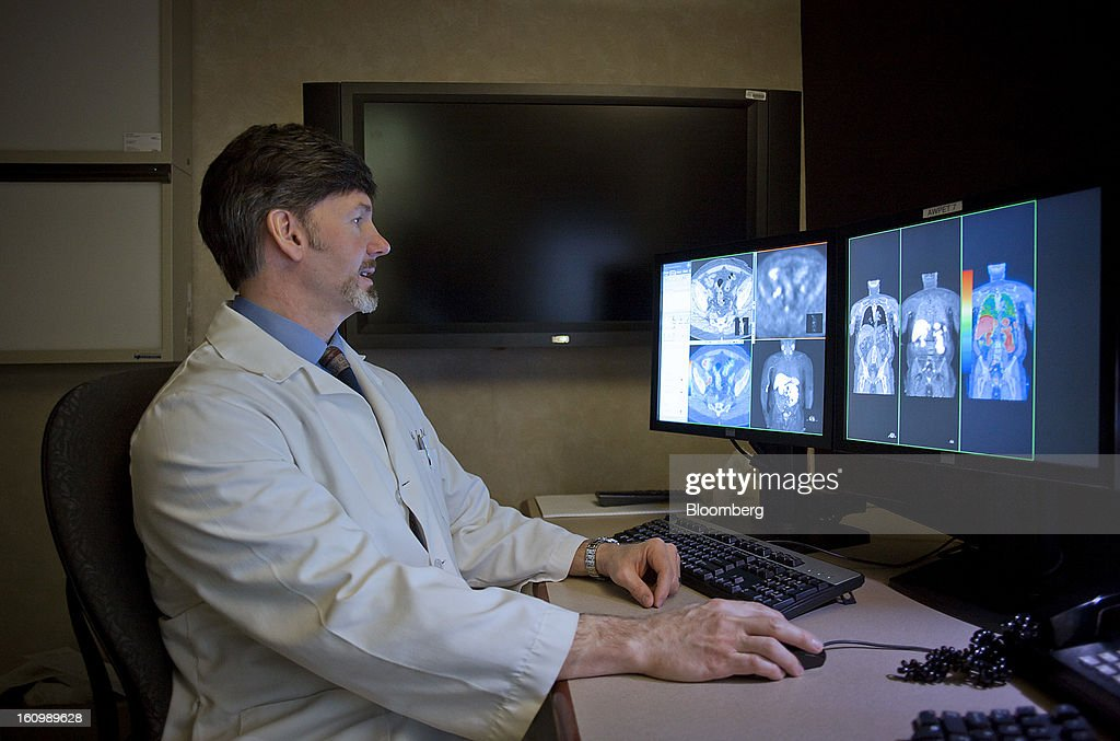 Radiologist Val J. Lowe, director of the cancer imaging program at the Mayo Clinic cancer center, compares a CT scan to a choline C-11 PET scan of a patient with recurrent prostate cancer at the Mayo Clinic medical center in Rochester, Minnesota, U.S., on Wednesday, Jan. 30, 2013. The Mayo Clinic, a nonprofit specializing in medical care, research and education, announced in January that it will join UnitedHealth Group Inc., the largest U.S. provider of medical coverage, in a research alliance designed to merge insurance records and medical data to find more efficient ways to deliver care. Photographer: Ariana Lindquist/Bloomberg via Getty Images