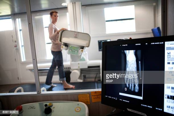Radiology center France technician carries out a foot xray on a patient who had an operation on a hallux valgus