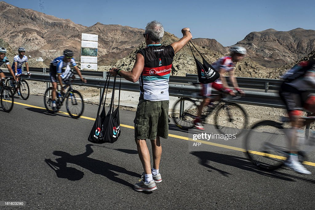A Radioshack Leopard member gives cyclists feeding bags in the feeding zone during the third stage of the Tour of Oman, from Nakhal Fort to Wadi Dayqah Dam, on February 13, 2013, in Oman. The six-stage race, which follows the Tour of Qatar, won by Britain's Mark Cavendish last week, culminates on February 16 at Matra Corniche.