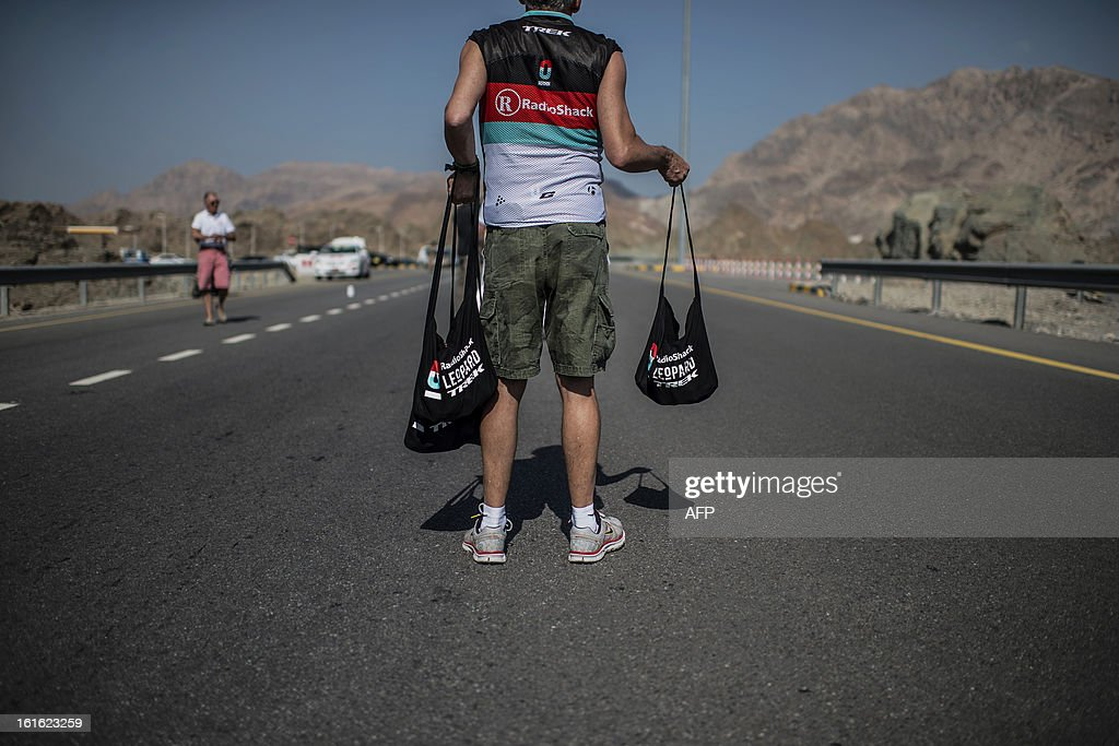 A Radioshack Leopard member waits for cyclists in the feeding zone during the third stage of the Tour of Oman, from Nakhal Fort to Wadi Dayqah Dam, on February 13, 2013, in Oman. The six-stage race, which follows the Tour of Qatar, won by Britain's Mark Cavendish last week, culminates on February 16 at Matra Corniche.