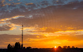 Radio waves escaping from gsm tower   visualisation at sunset in rural area