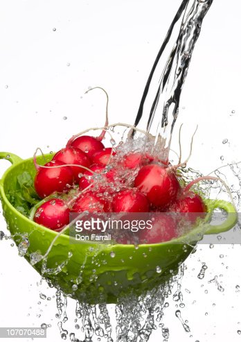 Radishes in a colander with a splash of water